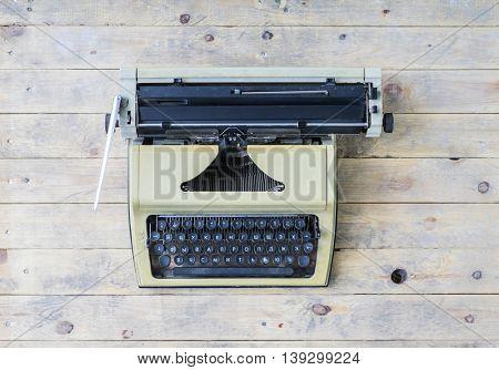 Retro typewriter over vintage wooden background.