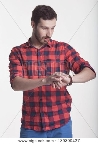 Handsome young man looking at his watch running late on grey background.