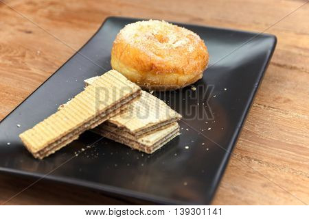wafer stick and donuts sugar on black dish with wood background. selective focus.