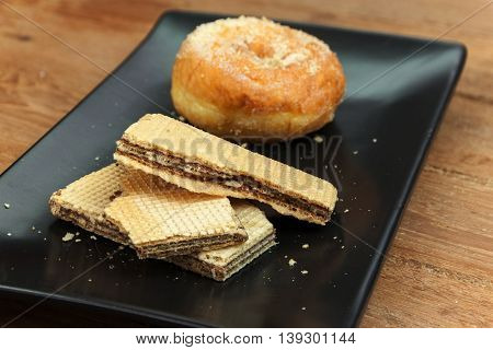 wafer stick and donuts sugar on black dish with wood background