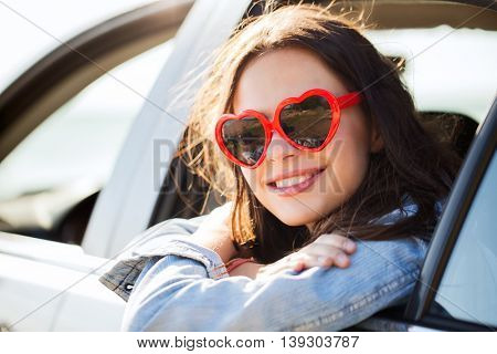 summer holidays, valentines day, travel, road trip and people concept - happy teenage girl or young woman heart shaped sunglasses in car