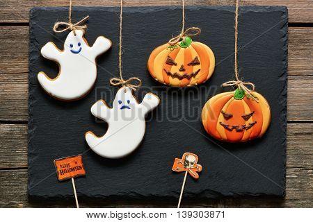 Halloween homemade gingerbread cookies over slate background