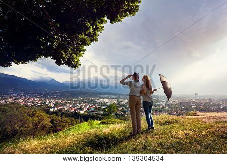Two friends with umbrella looking to the beautiful view of city panorama in the mountains at rainy dramatic sunset