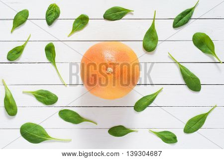 Fruit pattern. Baby spinach leaves and red grapefruit on white wooden planks background. Flat lay of fresh healthy food ingredients. Healthy green vegan lifestyle concept. Deconstructed spinach grapefruit smoothie