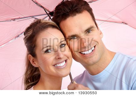 Happy Smiling Couple Under A Pink Umbrella