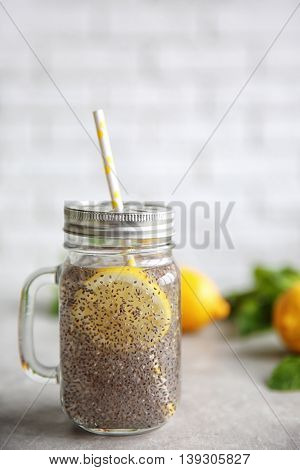 Chia seeds drink with lemon and mint in glass jar on table
