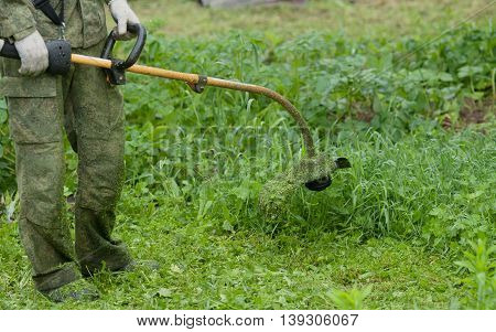 Photo of a young man mowing the grass with the trimmer