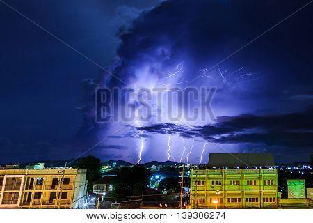 Thunderstorm over city showing multiple lightning strikes.