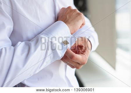 Male buttons cufflinks. Businessman buttons cufflinks in white shirt. Groom in morning wears shirt to a wedding.