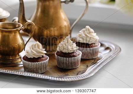 Tasty cupcakes with tea set on silver tray