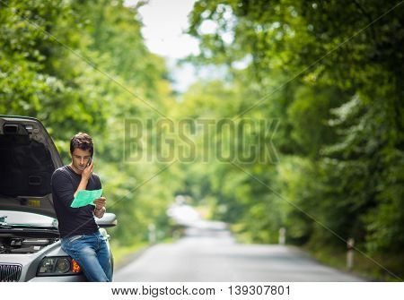 Handsome young man calling for assistance with his car broken down by the roadside