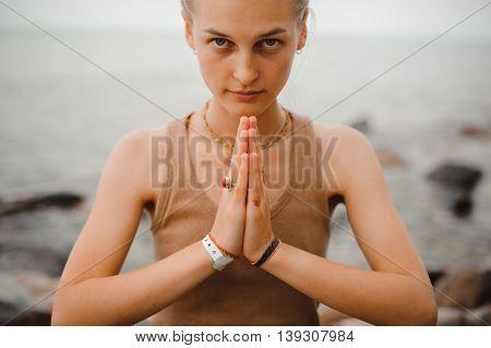 beautiful woman performing namaste gesture on beach
