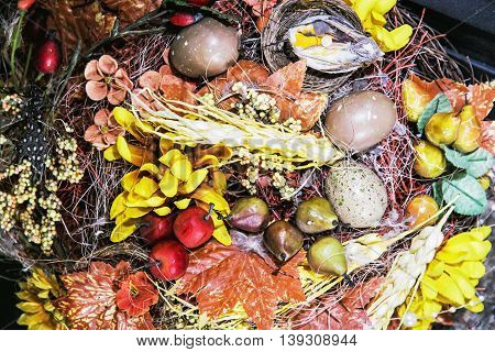 Seasonal colorful interior decoration. Bird easter eggs red apples pears and various leaves. Beautiful symbolic decorative objects.