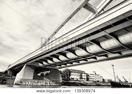 Modern Apollo bridge in Bratislava Slovak republic. Architectural theme. Danube river. Black and white photo. Ship transportation. Infrastructure theme.