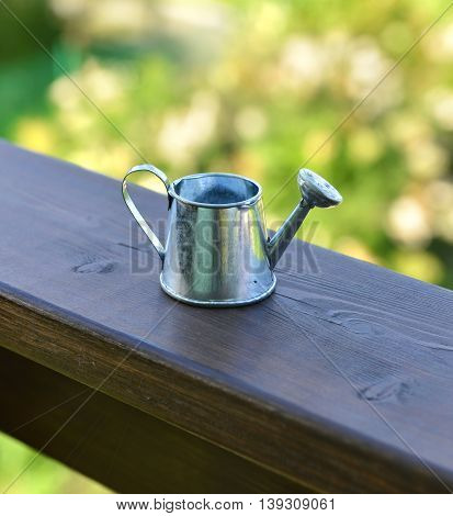 Close up of cute small watering can on wooden planks in the garden. Summer seasonal background, rural countryside still life, vintage or retro concept