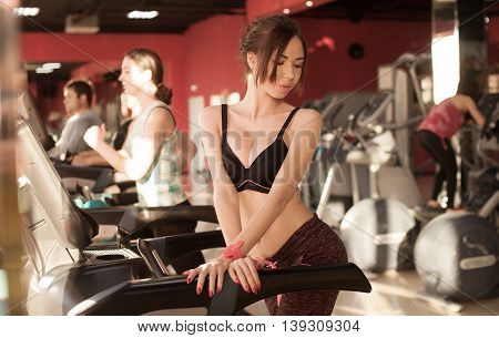 Pretty woman on treadmill in gym. Sunny color. Blurred background.