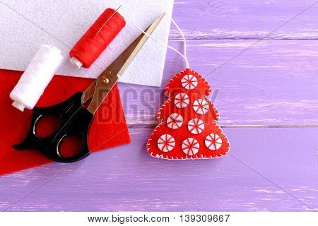 Red felt Christmas tree ornament, scissors, red and white felt sheets, thread, needle lilac on wooden background with blank space for text. Home decor. Crafts idea for Christmas
