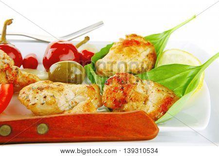 served roast chicken brisket on green leaf of basil
