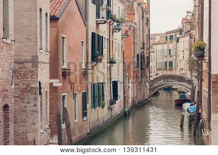 VENICE, ITALY - MARCH 17, 2016. Urban canal and boats on it, on a gloomy day in Venice, Italy. Vintage filter.
