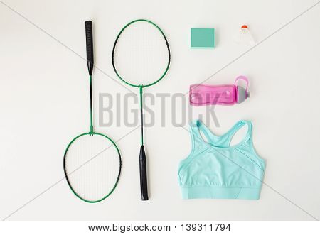 sport, fitness, healthy lifestyle and objects concept - close up of badminton rackets with speaker and sports stuff over white background