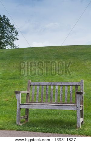 Empty wooden bench. Hill with a green grass in the background. Cloudy sky. Meijer Garden in Grand Rapids Michigan United States.