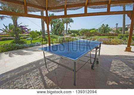 Ping pong table tennis game under gazebo in tropical gardens of luxury hotel resort