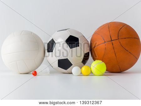 sport, fitness, game, sports equipment and objects concept - close up of different sports balls and shuttlecock
