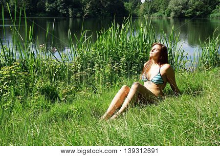 young woman wearing bikini basking in the sun with closed eyes