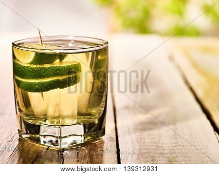 Alcohol drink. On wooden boards standing glass with alcohol green transparent drink. A drink number one hundred eighty three cocktail green tea with slice lime. Country life. Light background.