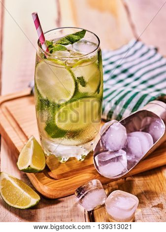 Alcohol cocktail. On wooden boards glass with alcohol cocktail and ice cubes. Drink number one hundred eighty nine cocktail mohito and scoop ice . Country life. Outdoor. Boards background.