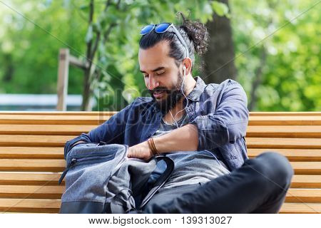 travel, tourism, lifestyle and people concept - man with earphones and sunglasses sitting on city bench and looking for something in his backpack