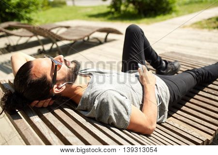people, music, technology, leisure and lifestyle - hipster man with earphones and smartphone listening to music on city street bench