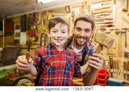 family, carpentry, woodwork and people concept - happy father and little son with hammer and chisel working at workshop