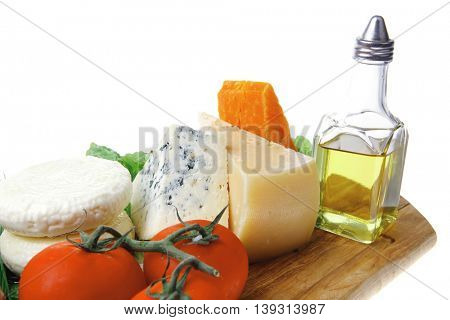 roquefort with cheddar, parmesan and soft feta cheese on wooden board with tomatoes bread and olive oil isolated over white background