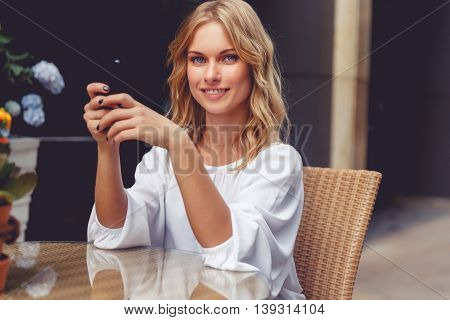 Portrait of beautiful blonde young woman in cafe with phone. Model smiling and looking at camera. Split toned photo