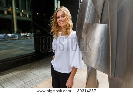 Smiling caucasian woman with curly blonde hair stands next to the steel sculpture and looking at camera