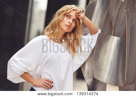 Sad young blonde woman in white blouse around the steel figures outdoors