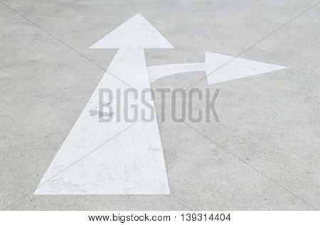 Closeup white painted arrow sign on cement street floor background sign in go straight and turn right direction