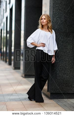 Thoughtful blonde woman in white blouse and black trousers in street near the building