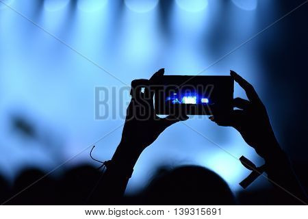 Person Capturing A Video On A Mobile Phone At A Music Festival