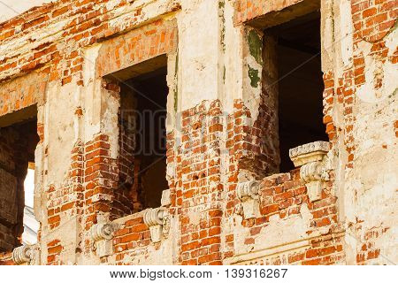 Empty windows in brick wall of an abandoned medieval manor, background photo texture