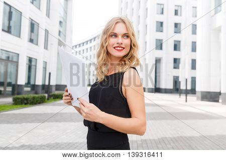 Lovely young stylish lady in black blouse and with papers in hand