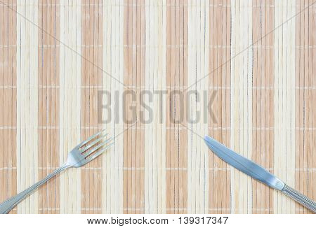 Closeup stainless fork and knife on wood mat textured background with copy space
