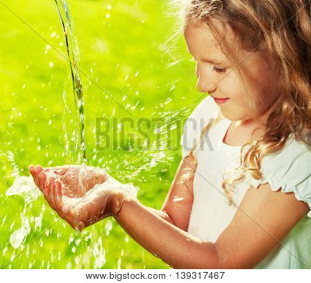 Stream of clean water pouring into children's hands. Child play with water