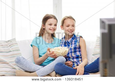 people, children, television, friends and friendship concept - two happy little girls with popcorn watching tv at home