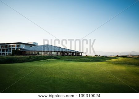 Beautiful golf club house with rays of sun and mountains at sunset