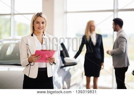 Elegant beautiful salesperson working at car dealership