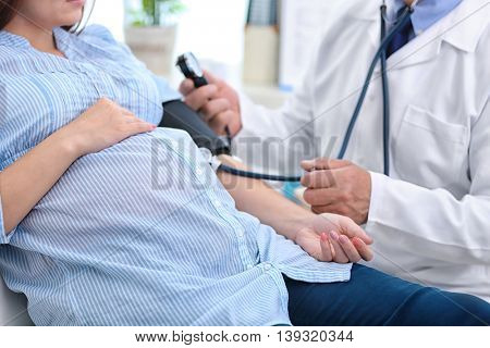 Doctor measuring pressure of the pregnant woman
