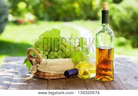 White wine and grapes on garden table
