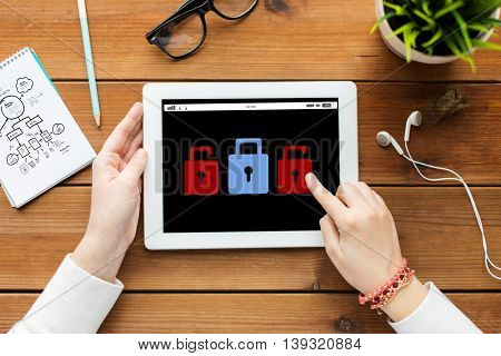 business, education, technology, people and cyber protection concept - close up of woman with lock icon on tablet pc computer screen on wooden table